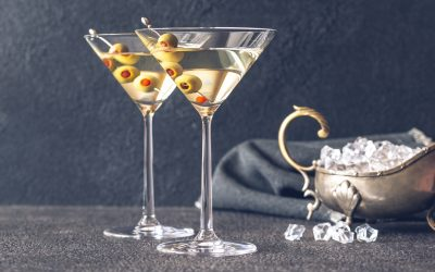 Two glasses of martini cocktail garnished with green olives